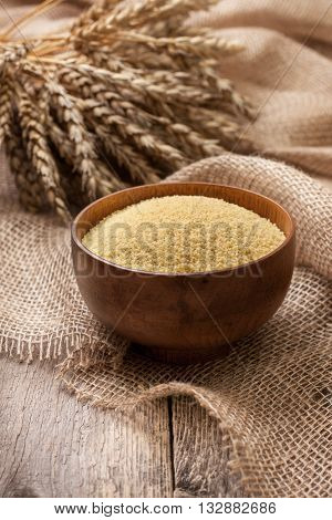 Couscous in a wooden bowl on a wooden background and sacking