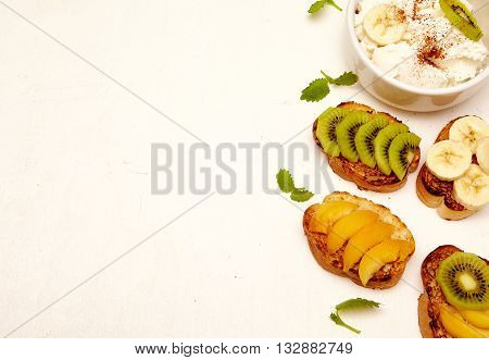 Various fruit sandwiches with banana kiwi apple apricot and ricotta. Healthy organic and vegan breakfast on white background. Top view copyspace.