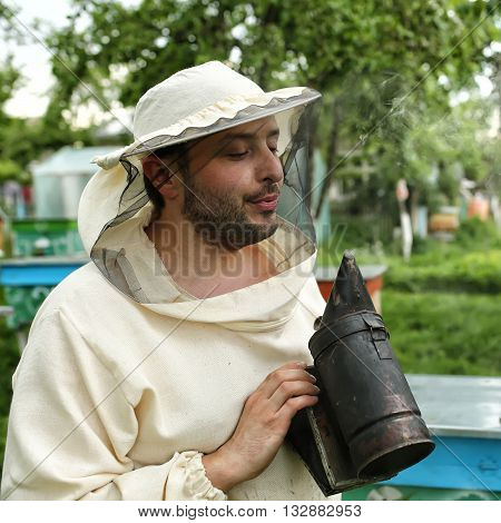 beekeeper in protective clothing holding smoker while standing at apiary