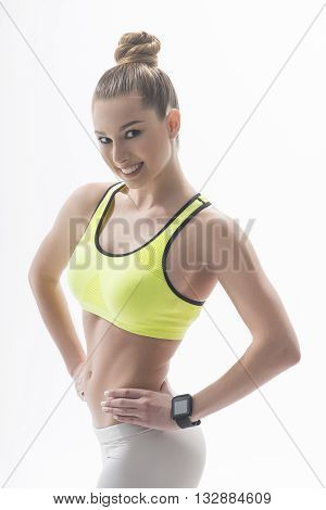 Attractive muscular female bodybuilder is showing her fit figure. Woman is standing and smiling. She is posing with arms akimbo. Isolated
