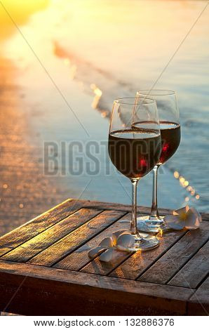 Romantic beach scene: two glasses of red wine at sunset near water line