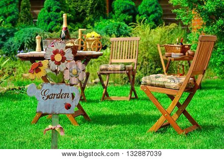 Sign Garden On The Wooden Plate And Wooden Outdoor Furniture