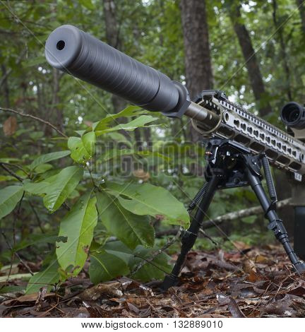 Silencer mounted on a semi automatic rifle in a forest