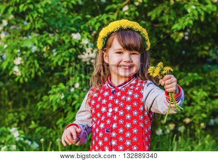 Joyful girl with a wreath of dandelions on her head and a bouquet of dandelions in hand on background of green tree in summer Park