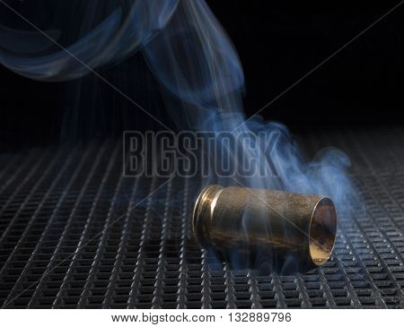 Brass that is emptied from a semi auto handgun with smoke rising