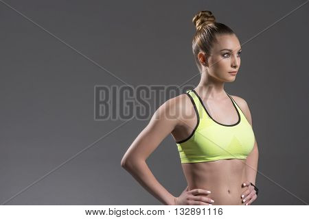 Portrait of pretty young woman going for sports. She is standing with arms akimbo. The athlete is looking forward confidently. Isolated and copy space in left side