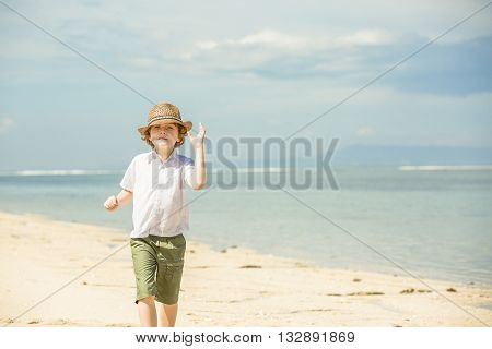 Happy caucasian boy with red hair in hat enjoing summer on tropical beach