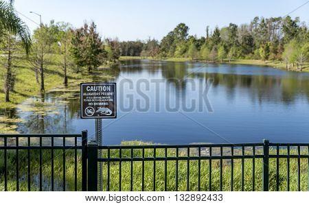 Lake with alligators in Florida. Signpost prohibiting swim