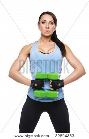 Beautiful sporty woman in sportwear making exercise with green dumbbells. Isolated over white background.