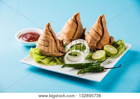 samosa on a plate with lemon, onion and green fried chili