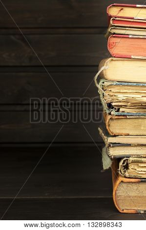 Front view of old books stacked on a shelf. Books without title and author. Old books in the university library. Books to study. Preparation for the exam in college.