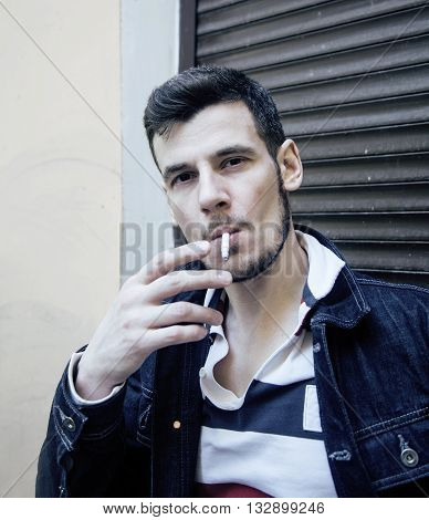 middle age man smoking cigarette on backjard, real stylish tough guy, lifestyle people concept