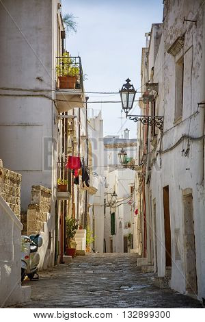 Narrow and old street or alley in italian town of Ostuni in Puglia. Historical view of Italy
