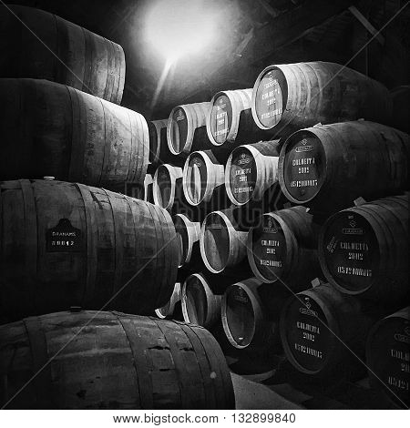 PORTO PORTUGAL - MAY 2 2015: Barrels or pipes of vintage port wine are stacked up in a cellar at Graham's storage facility in the city of Porto in Portugal.