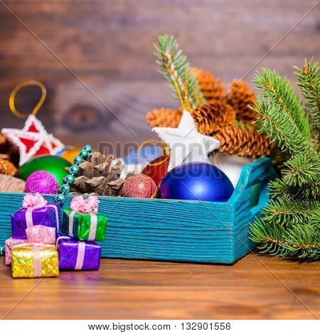 composition of branch fir tree vintage wooden box with Christmas decoration pinecones stars balls and gifts on wooden background closeup