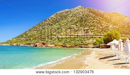 Sunny sandy Livadi beach in sea Bay of resort village Bali. Views of mountain shore washed by waves and sun loungers with parasols where sunbathing tourists. Bali Rethymno Crete Greece