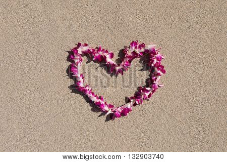 orchid flower garland necklace in love heart shape on white sand beach, romantic couple honeymoon trip at Hawaii