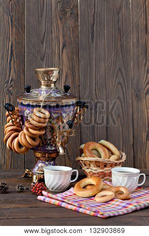 Russian traditional samovar with colorful donut and a cup of tea with bagels on a wooden background