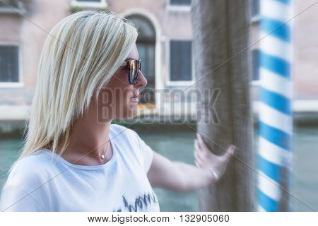 Beautiful blonde woman portrait with hand on pier. Beautiful blonde girl wearing sun glasses and gold necklace in Venice with blurred zoom effect on background.
