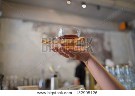 hand carrying hot tea in coffee shop hand showing hot tea woman hand and hot tea