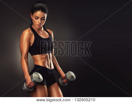 Beautiful fitness woman lifting dumbbells . Fitness sporty girl showing her well trained body . A beautiful girl body with rippling muscles from strength training .