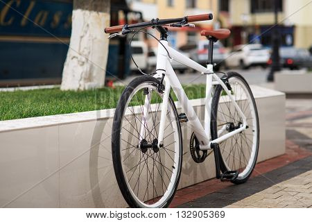 A white fixed-gear bicycle on street. Low angle