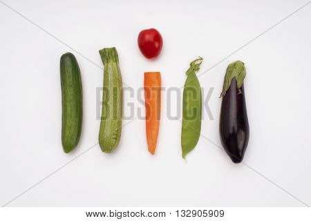Mini cucumber, courgette, carrot, cherry tomato, peas and aubergine side by side. Set of minimalistic vegetables isolated on white looking like an exclamation mark