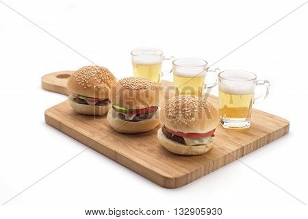 Mini burgers and and beer shots on a wooden serving board isolated on white. Party food.