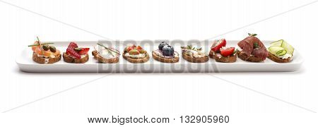 Party finger food, small bite sized canapes on a white porcelain plate isolated on white