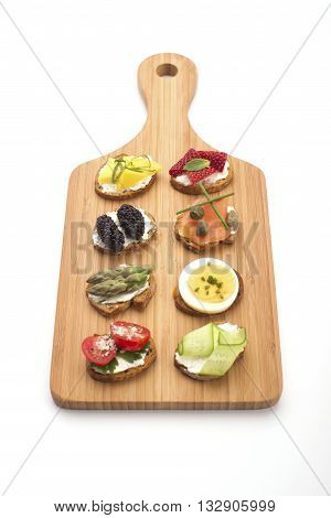 High angle view of bite size canapes on a wooden serving board. Party food crackers isolated on white.