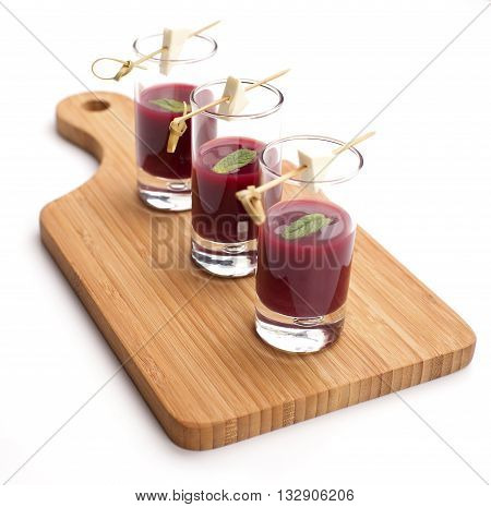 Cheese and beetroot sauce snacks in shot glasses served on a wooden board with crackers. Party food isolated on white.