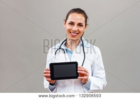 Female doctor showing digital tablet and looking at camera.