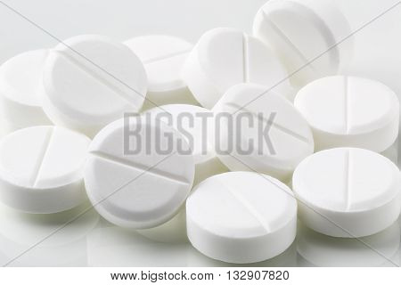 Bunch of white round pills and drugs on white background