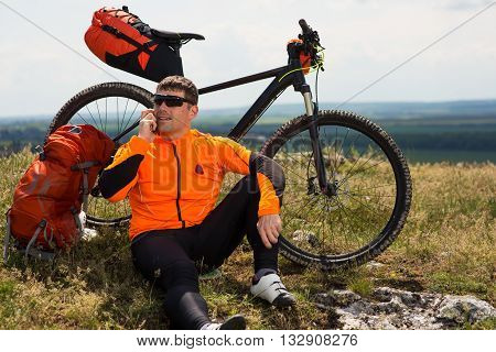 Young Man Cyclist in Orange Clothes Talking On Cell Phone Against Blue Sky