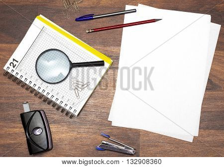 stationery consisting of notebook pen loop staples stapler and hole punch on the table