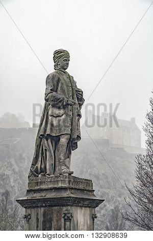 Allan Ramsay Statue and Edinburgh castle covered in mist in the background.