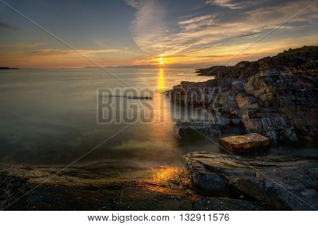 Rocky coast of Cuan Sound with sunset in background Highland Scotland