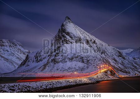 Flakstadoya bridge with light trace after passing truck in mountains Lofoten