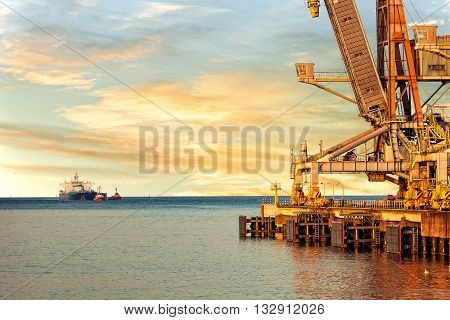 Industrial crane on a wharf waiting to be loaded onto ship.