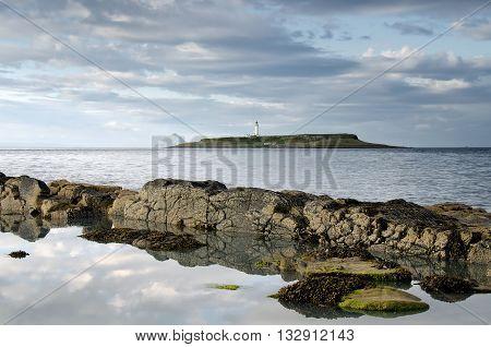 Pladda lighthouse with rocky coastline reflections Isle of Arran Scotland