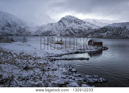 Rorbu and boat in little harbor among snowy mountains Lofoten