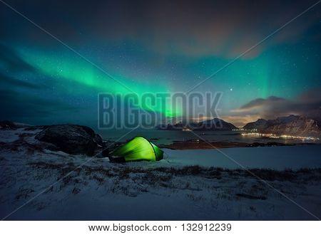 The green tent camping under Aurora borealis near Ramberg Lofoten