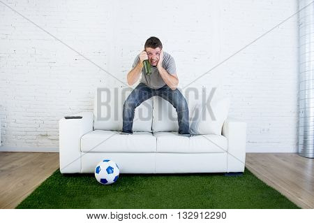 crazy football fan cheering watching television soccer match suffering stress nervous and excited jumping on sofa couch with ball and grass carpet emulating stadium pitch