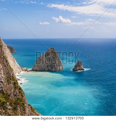Two sharp rocks protrude from the water on the coast of the island of Zakynthos. Greece.