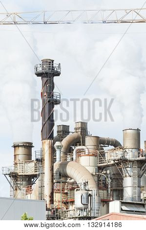 Industrial plant of a furniture factory with smoking ,smokestack tube and silos.