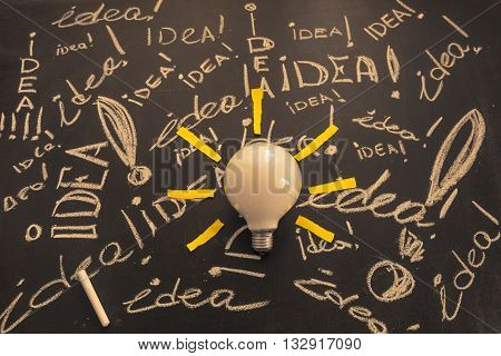 Light bulb with rays made from yellow stickers on the brawn chalkboard with titles idea! written by white chalk light bulb idea business idea business concept Innovation concept