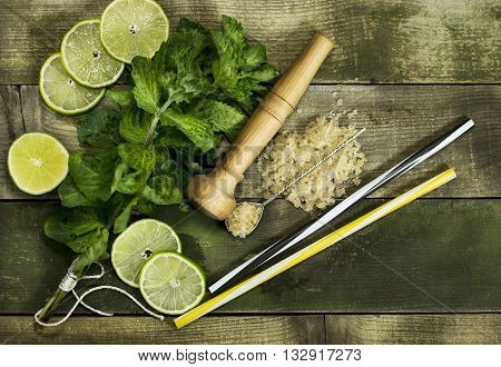 Set for Mojito - limes mint leaves hammer on the wooden background.