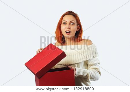 Smiling emotional Woman hold gift box.  White wall background. Red gift box.