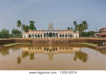 Chettinad India - October 17 2013: Kothamangalam Shiva Temple reflected in temple pond filled with brown water. Vimanam tower in the back. Green trees. All against blue sky.