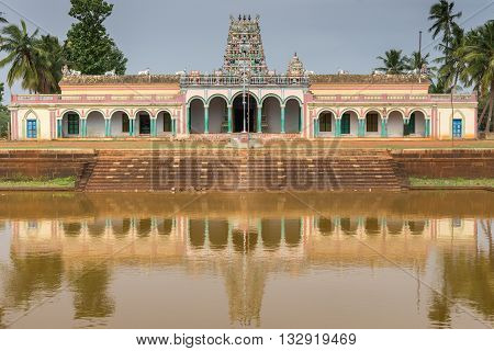 Chettinad India - October 17 2013: Closeup of Kothamangalam Shiva Temple reflected in temple pond filled with brown water. Vimanam tower in teh back. Green trees. All against blue sky.